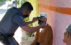 Policiais militares orientam idosos na colocação de máscaras de proteção em Araçatuba